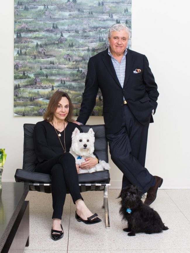 "Charles and Joanne Teichman, the owners of Ylang 23, at home in Preston Hollow with the family dogs, Tuey (white) and Eddie (black).  The Teichmans bought Neil Raitt's painting, ""Cabinectomy"",  from The Goss-Michael Foundation.  Photography by Mei-Chun Jau for FD Magazine."